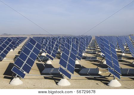 solar field with blue and cloudy sky