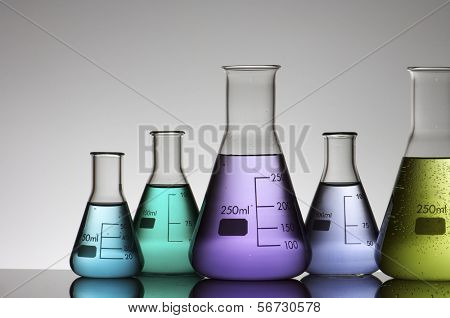 group of conical flasks containing liquid shiny