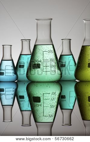 group of conical flasks containing liquid in shades of green
