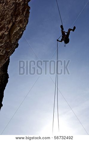 climber descending with the technique of rappelling