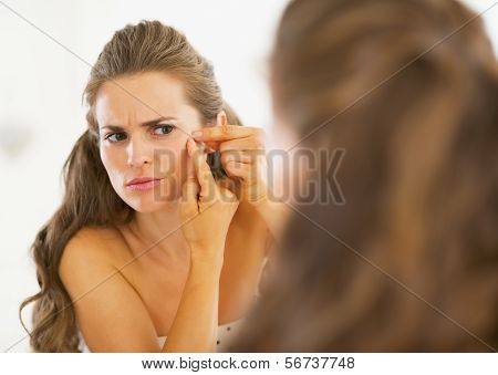 Frustrated Young Woman Squeezing Acne