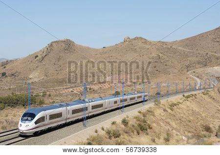 view of a high-speed train crossing a arid landscape in Purroy, Saragossa, Aragon, Spain; AVE Madrid Barcelona