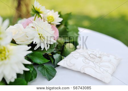 Wedding Rings On A White Pillow Near Flowers