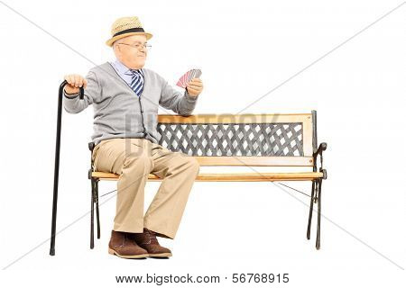Senile old man with cane, sitting on bench imagining playing cards with someone else, isolated on white background