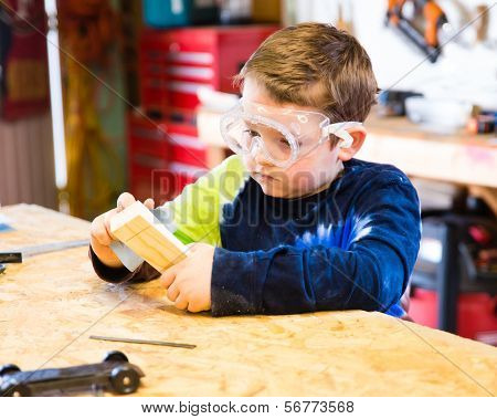 Boy Sanding Wooden Block In Workshop As He Builds Car For Pinewood Derby