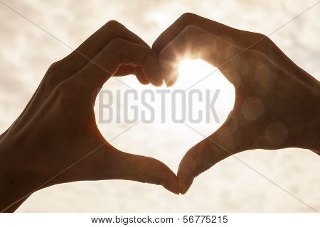 Hand heart shape silhouette made against the sun & sky of a sunrise or sunset