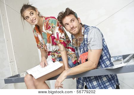 Happy young couple building new house, looking at floor plan, sitting on iron bar.