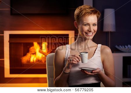 Happy young woman drinking coffee by fireplace in cosy room.