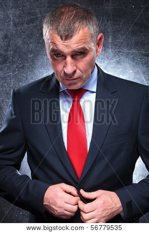 dramatic serious mature business man unbuttoning his coat, studio shot
