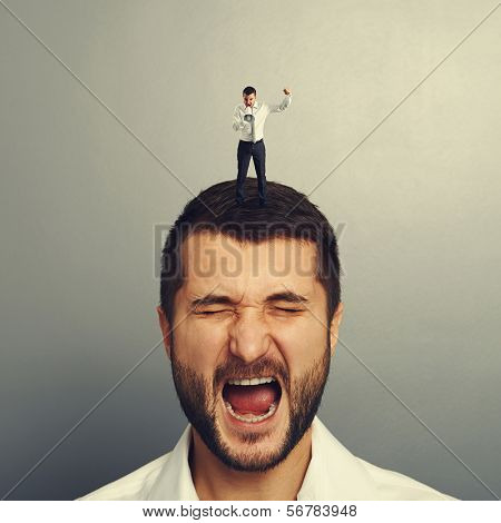 small angry boss standing on the head and screaming at worker over grey background