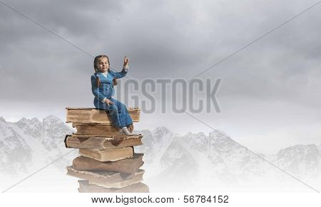 Image of cute school girl in sitting on pile of books