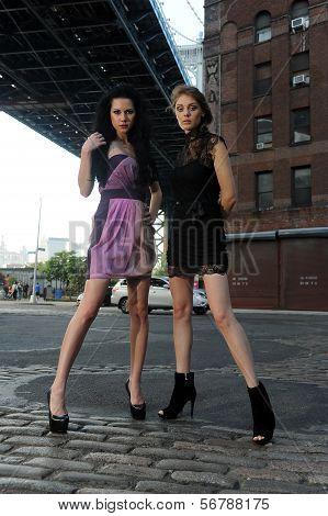 Two models posing under Manhattan bridge