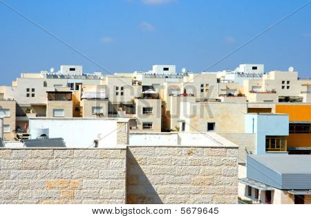 Flat roofs of new yellow apartment buildings under blue sky