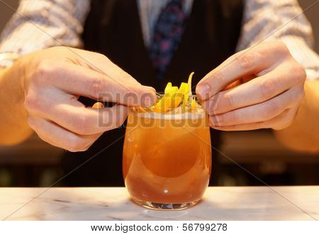 Barman is decorating cocktail with lemon zest