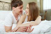 Постер, плакат: Романтическая пара лежа в постели и глядя друг на друга
