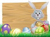 stock photo of peek  - Easter wood sign with the Easter bunny and decorated Easter eggs - JPG