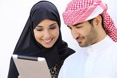 stock photo of arab man  - Happy saudi arab couple looking a tablet together on a white wall background - JPG