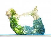 picture of stretching exercises  - Combining nature with spiritual yoga in a creative portrait of a young woman lying with her body arched holding her toes and her eyes closed in serenity - JPG