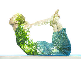 stock photo of superimpose  - Combining nature with spiritual yoga in a creative portrait of a young woman lying with her body arched holding her toes and her eyes closed in serenity - JPG
