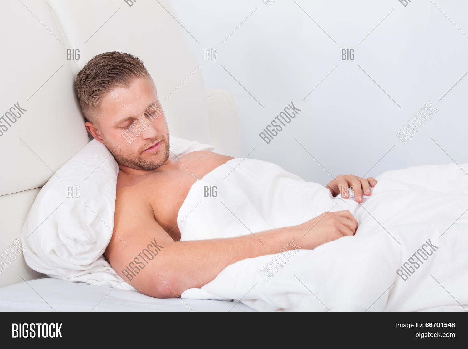 Man Sleeping In Bed Propped Up Against The Pillows