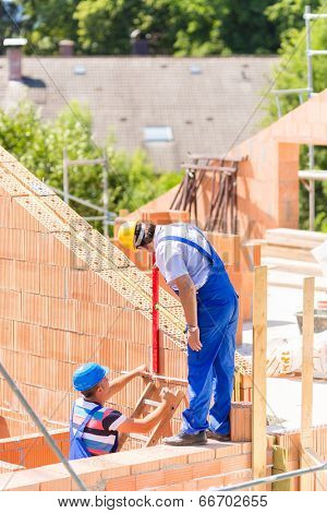 Two builder or worker with helmets controlling walls in scaffold with a bubble level on building or construction site