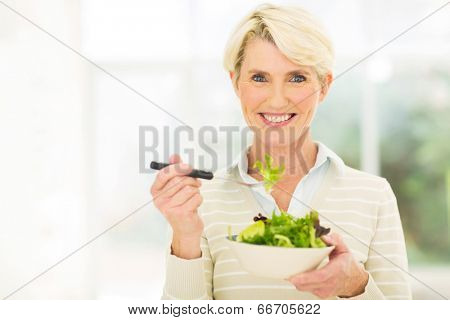 beautiful senior female vegetarian eating salad