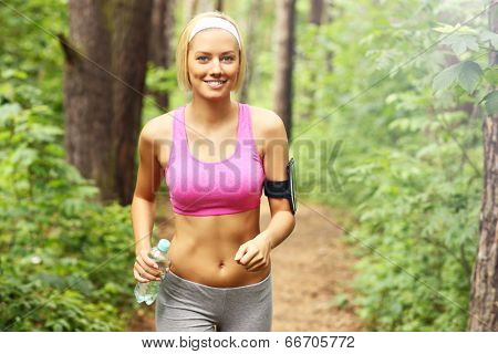 A picture of a woman jogging in the forest with a bottle of water