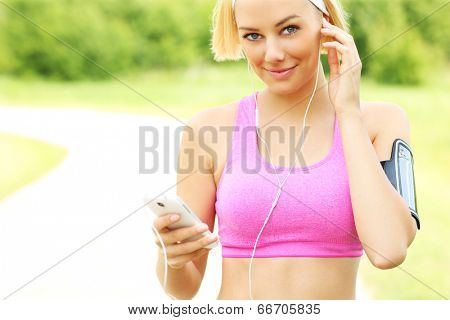 Young fit woman listening musing during running in the park