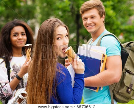 Group of multi ethnic students eating ice-cream outdoors