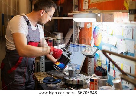 Serviceman mixing paint in a car body workshop