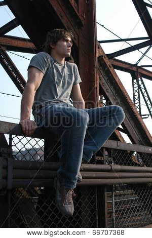 Young worker sitting on metal constructions