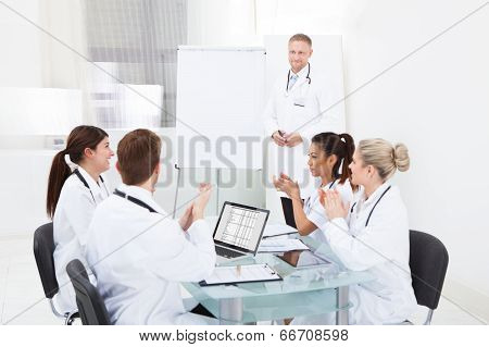 Doctors Clapping For Colleague After Presentation