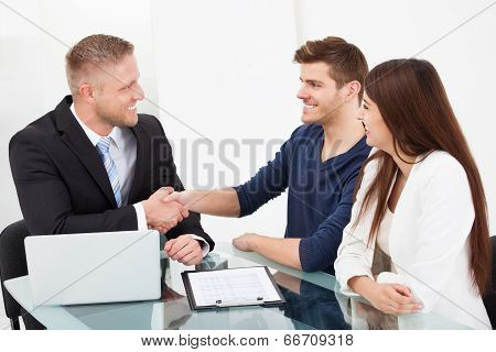 Financial Advisor Shaking Hand With Couple
