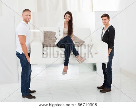 Movers Carrying Sofa With Client