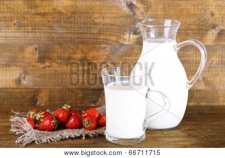 Ripe sweet strawberries in wooden bowl and jug with milk on color wooden background