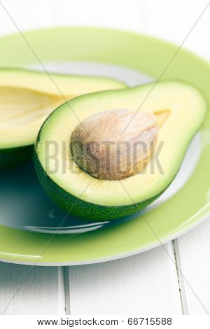 halved avocados on green plate