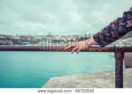 Woman Resting Her Hand On Rail In Harbour