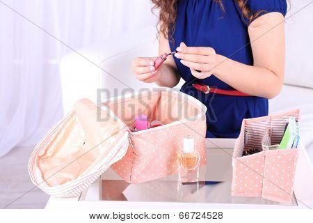Girl applying make up on home interior background