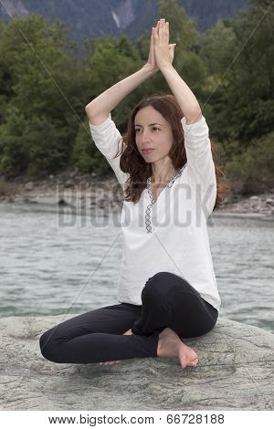 Woman In Namaste Pose Outdoors By A River