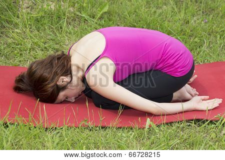 Woman In Childs Pose During Yoga Outdoors
