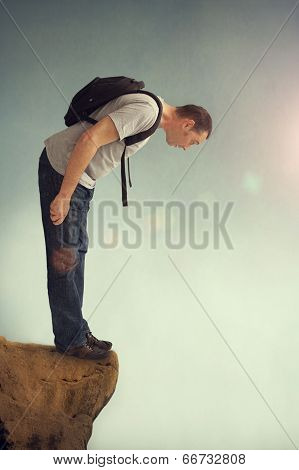 Man Looking Down From A Rocky Ledge