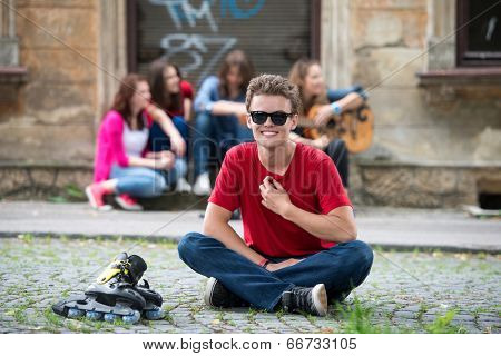 Happy teenager sitting with inline skates on the street