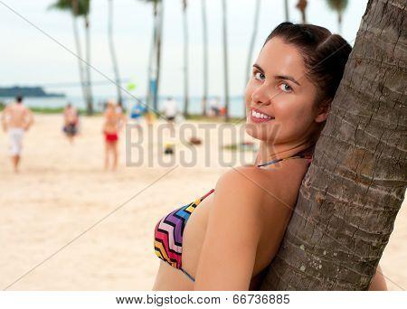 Woman standing near palm tree on the beach