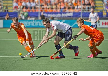 THE HAGUE, NETHERLANDS - JUNE 13: Dutch players Van Ass and De Wijn blocking England striker Simon Mantell during the semi-finals of the world championships hockey 2014. NED wins wity 2-1