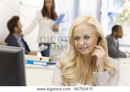 Portrait of beautiful young female dispatcher working in busy office, smiling.
