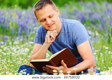 A Man Reads A Book In The Field.