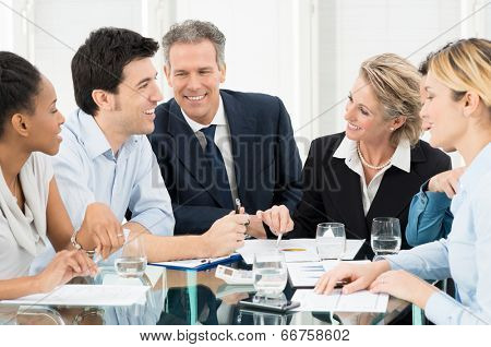 Portrait Of Happy Multiracial Businesspeople Discussing In Meeting
