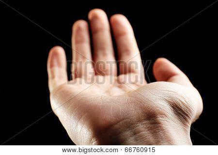 Human hand on black background