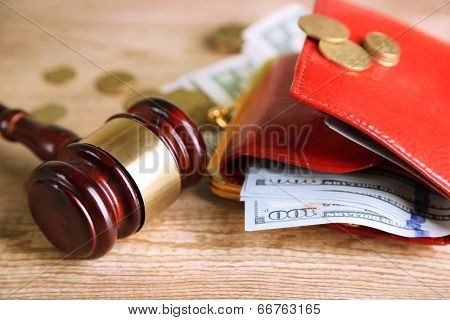 Gavel and money coins on wooden background