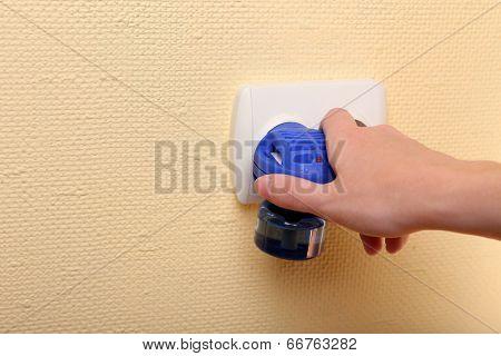 Hand holding mosquito fumigator